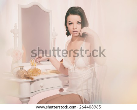 Gorgeous Young Woman in White Nightie Sitting at her White Room In Front of a Mirror While Looking at the Camera. - stock photo