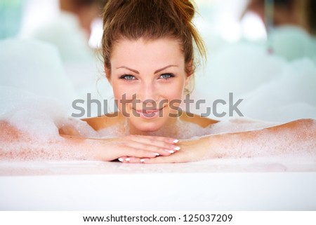Gorgeous young woman lying in a bath tub at home and relaxing - stock photo