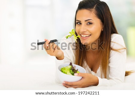 gorgeous young woman lying on bed eating vegetable salad - stock photo