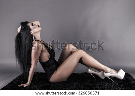 Gorgeous young woman lying on the floor over gray background, studio shot - stock photo