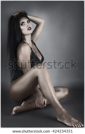 Gorgeous young woman lying on the floor over gray background, studio shot