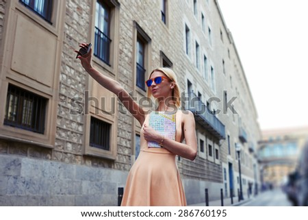 Gorgeous young woman making self portrait with a cell phone camera while enjoying a day out strolling in new city at summer vacation, stylish female hipster taking a picture of herself on smart phone - stock photo