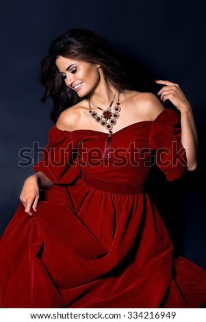 gorgeous young woman posing in a luxurious burgundy velvet dress