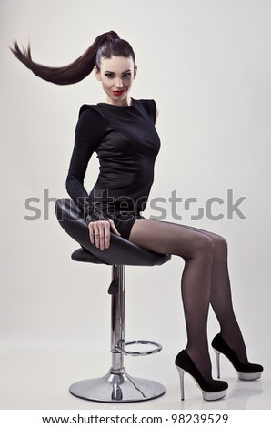Gorgeous young woman sitting on a chair - stock photo