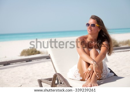 Gorgeous young woman sitting on the tropical beach in a sunbed, enjoying the summer sun. Glamorous girl with gold tattoo on the hand. - stock photo
