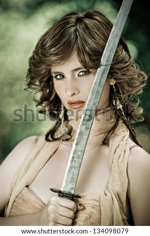 Gorgeous young woman striking a stance holding a sword in her hands while performing in the park - stock photo