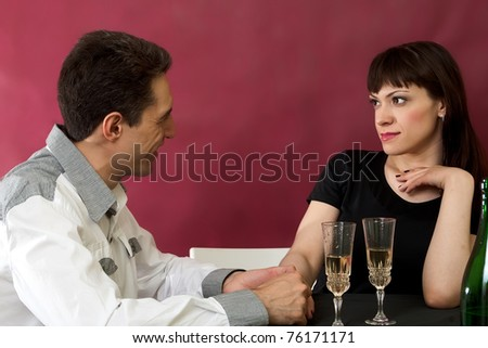 Gorgeous young woman surprised while sitting together with her boyfriend on red burgundy background - stock photo