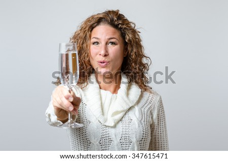 Gorgeous young woman toasting with champagne raising her flute to the camera with a happy smile as she celebrates a special event