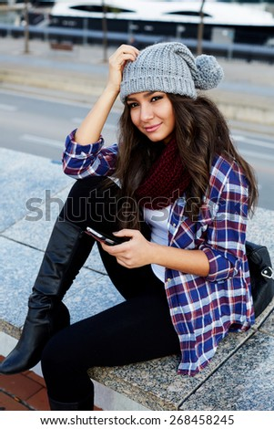Gorgeous young woman using smart phone while looking to the side outdoors, beautiful female student holding cellphone while sitting on the bench, hipster girl looking to someone in urban setting - stock photo