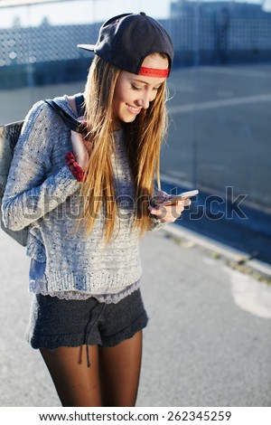 Gorgeous young woman wearing casual spring clothes walking down a city street while typing on her cellphone message, pretty girl walking outdoors in the street while using busy a smart phone - stock photo