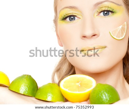 Gorgeous young woman wearing colorful make-up and holding slice of lemon