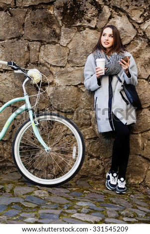 Gorgeous young woman, wearing in gray jacket, black pants, sneakers and scarf, with black bag, holding cup of coffee and smart phone, near retro bike, on the street of old European city, full body - stock photo
