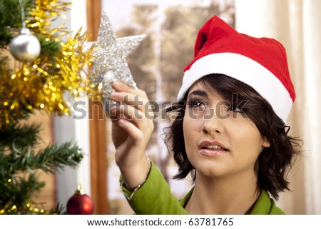 Gorgeous young woman with a Santa hat decorating the Christmas tree in her home. - stock photo