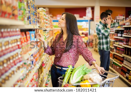 Gorgeous young woman with a shopping cart looking at some products on a supermarket aisle - stock photo