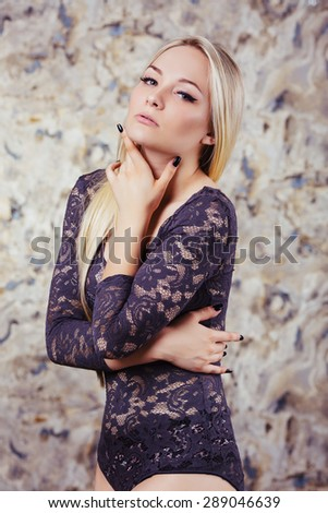 Gorgeous young woman with shiny long blond hair. Wearing fashionable sensual dark lingerie. Posing in studio. Model with make-up and perfect slim body. - stock photo