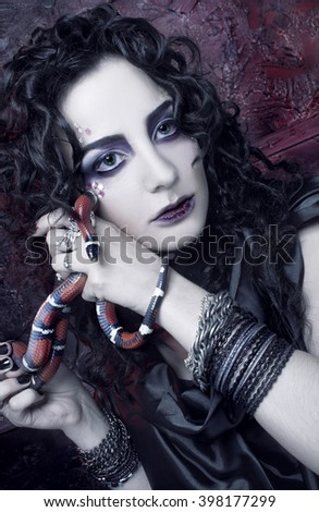 Gorgon. Young woman in dark creative image and with snake.
