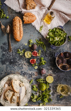 Gorgonzola cheese, figs, salad leaves and lime sliced over on blue rustic kitchen table. Rustic moody style. - stock photo