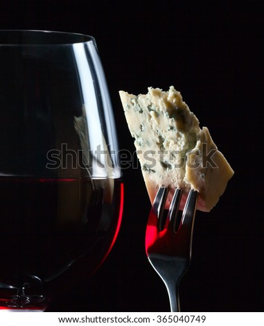 Gorgonzola on a fork and red wine on black background - stock photo