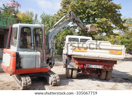 Gorna Oryahovitsa - October 17: Construction Site - Mini excavator dig a hole and loads of dirt truck on October 17, 2015, Gorna Oryahovitsa, Bulgaria