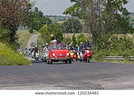 """GOROLO DI BORGHI (FC) ITALY - JUNE 3: an old Fiat 500 leads the group of scooter riders in rally of Italian scooters """"8�° Vespa Raduno Gorolo di Borghi"""" on June 3 2012 in Gorolo di Borghi, FC, Italy - stock photo"""