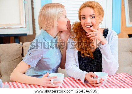 Gossip and girl talk. Two beautiful young women gossiping and drinking coffee while sitting in the cafe  - stock photo