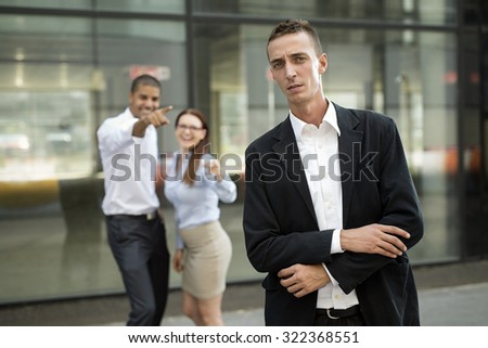 Gossip colleagues in front of their office, businessman portrait and gossiping out of focus in background.