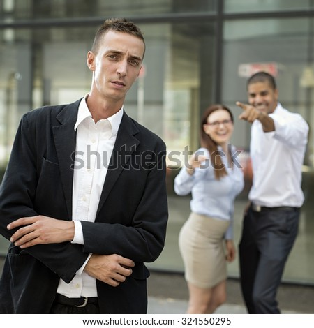 Gossip colleagues in front of their office, businessman portrait and gossiping out of focus in background. - stock photo