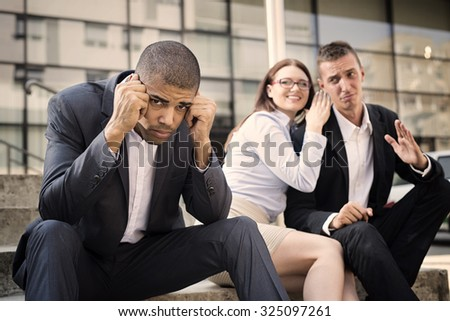 Gossip colleagues in front of their office sitting on stairs, depressed businessman portrait and gossip out of focus in background. Reason is racism. Shallow depth of field. - stock photo