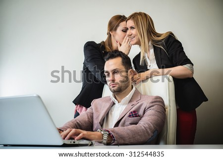 Gossip girls at office, handsome businessman working on laptop and gossip girls out of focus in background. - stock photo