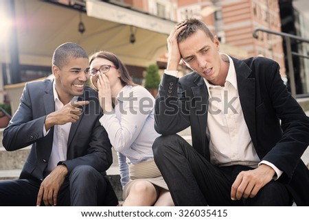 Gossip people in front of their office sitting on stairs,depressed businessman portrait and gossip out of focus in background. - stock photo