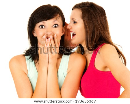 gossip, young woman whispering to the friends ear, white background - stock photo