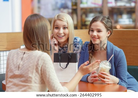 Gossiping by the cocktail. Close up of two attractive young women drinking cocktails in shopping mall and having a talk with their friend sitting in front of them - stock photo