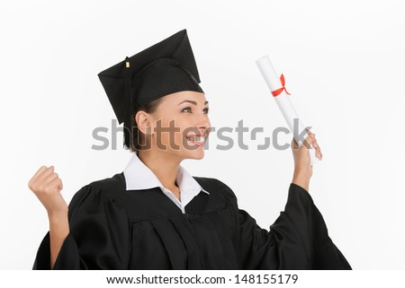 Got my degree. Happy young women in mortarboard holding diploma and gesturing while isolated on white