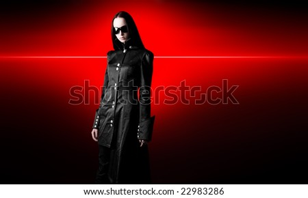 Goth woman in black cloak. On red shine background. - stock photo