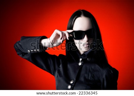 Goth woman with sunglasses. On red background. - stock photo
