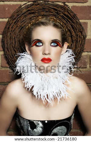 Gothic beautiful woman with feather necklace and false lashes wearing red lips - stock photo