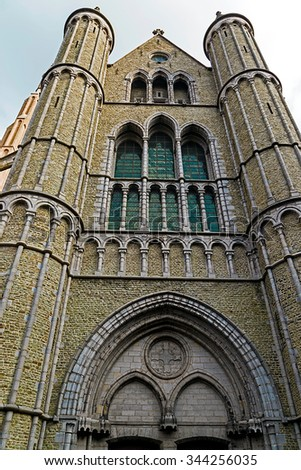 Gothic facade and tall belfry of the Church of Our Lady, Bruges, Belgium. - stock photo