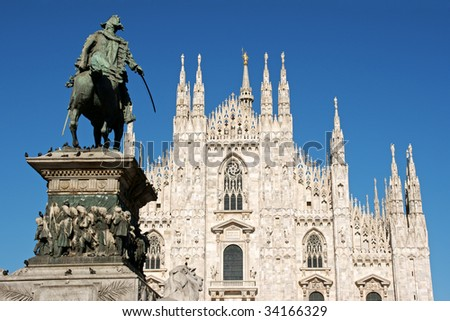 Gothic facade of Milan Cathedral in Piazza del Duomo. It is the fourth largest church in the world. On the left the monument to king Vittorio Emanuele II. - stock photo