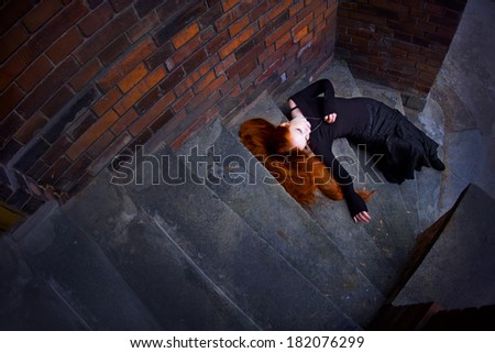 Gothic girl dressed in black lie on stairway - stock photo