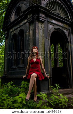 Gothic girl walking through cemetery looking away - stock photo