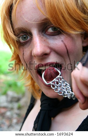 Gothic girl with chains in her mouth - stock photo