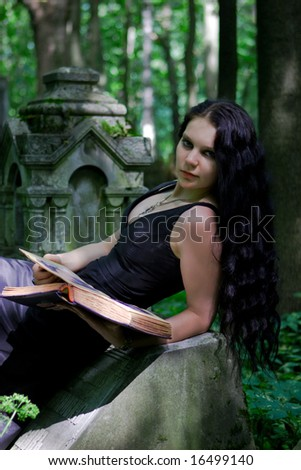 Gothic girl with old book posing on gravestone - stock photo
