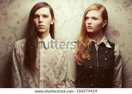 Gothic hipsters concept. Portrait of beautiful long haired people looking like dolls in vintage style: handsome guy with brown hair and gorgeous red-haired girl posing together. Studio shot - stock photo