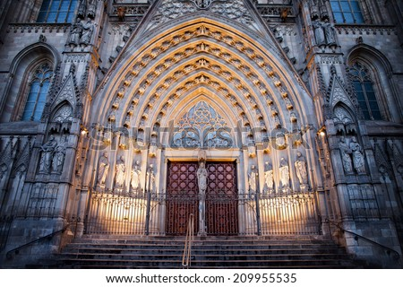 Gothic style portal to the Barcelona Cathedral illuminated at night in Catalonia, Spain. - stock photo