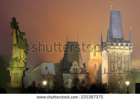 Gothic towers and sculptures on the Charles bridge illuminated by night, Prague, Czech Republic - stock photo