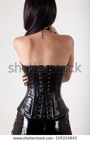 Gothic woman in black leather corset embracing herself - stock photo