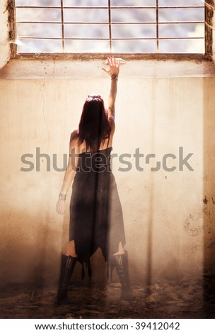 Gothic young woman raising hand towards light. - stock photo