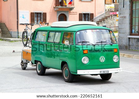 GOTTHARD PASS, SWITZERLAND - AUGUST 5, 2014: German classic van Volkswagen Transporter at the high Alpine mountain road. - stock photo