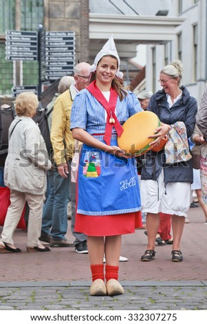 GOUDA-HOLLAND-AUGUST 21, 2014. Traditional dressed Dutch girl on a cheese market. Gouda has a regular traditional merchant post-medieval style cheese market, re-enacted during summer for tourists. - stock photo