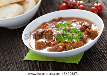 goulash in a bowl with bread